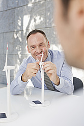 Germany, Leipzig, Business people discussing about wind power model - WESTF018545