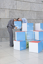 Germany, Leipzig, Business people resting on cubes - WESTF018593