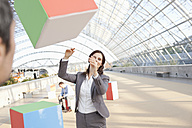 Germany, Leipzig, Business people playing with cubes - WESTF018605