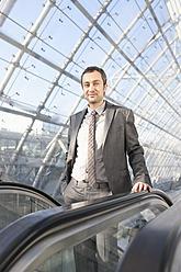 Germany, Leipzig, Businessman on escalator, portrait - WESTF018635