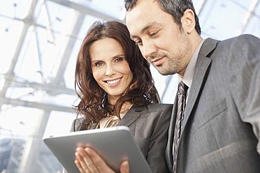 Germany, Leipzig, Business people using digital tablet - WESTF018641