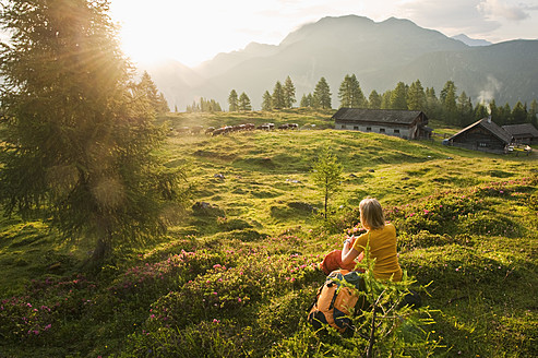 Austria, Salzburg County, Young woman sitting in alpine meadow and watching landscape - HHF004010