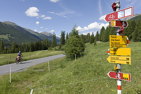 Switzerland, Mature man cycling on country road, directional sign in foreground - DSF000396