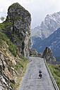 Switzerland, Mature man cycling through mountain road - DSF000401