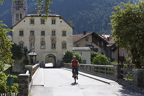 Austria, Mature man cycling on bridge, Pfunds in background - DSF000403