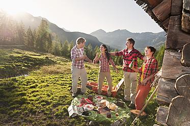 Austria, Salzburg County, Men and women having picnic near alpine hut at sunset - HHF004034