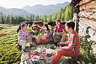 Austria, Salzburg County, Men and women having picnic near alpine hut at sunset - HHF004036