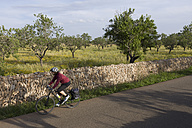 Spain, Mallorca, Woman cycling through country road - DSF000407
