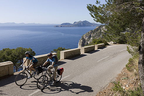 Spain, Mallorca, Man and woman cycling on road at Cap de Formento - DSF000416