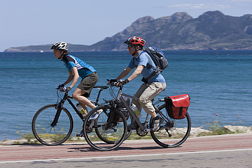 Spain, Mallorca, Man and woman cycling through road by sea - DSF000419