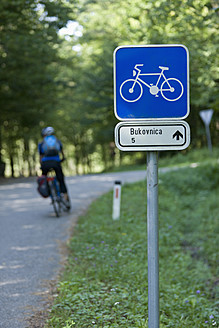 Slovenia, Bukovnica, Mature man cycling beside road sign - DSF000422