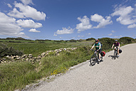Spain, Menorca, Cavalleria, Man and woman cycling through country road - DSF000513