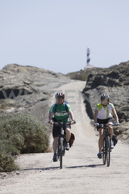 Spain, Menorca, Man and woman cycling, Cap de Favaritx in background - DSF000516