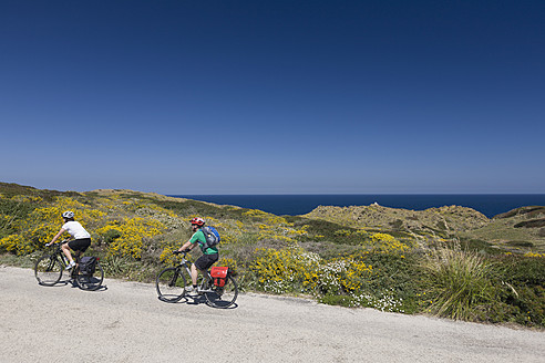 Spain, Minorca, Man and woman cycling by sea - DSF000519