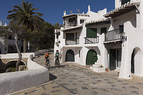 Spain, Minorca, Binibeca, Man and woman cycling through promenade - DSF000497