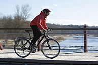 Germany, Bavaria, Munich, Mid adult woman riding bicycle - DSF000479