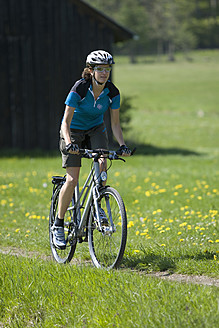 Germany, Bavaria,  Mid adult woman riding bicycle - DSF000476