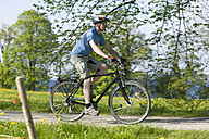 Germany, Bavaria, Mature man riding bicycle - DSF000472