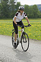Germany, Bavaria, Mid adult woman riding bicycle - DSF000469