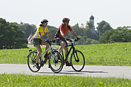 Germany, Bavaria, Man and woman riding bicycle - DSF000466