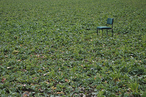 Germany, View of green chair in field - AXF000013