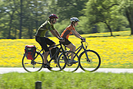 Germany, Bavaria, Man and woman riding bicycle - DSF000539