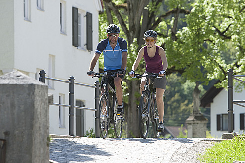 Germany, Bavaria, Man and woman riding bicycle - DSF000545
