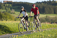 Germany, Bavaria, Man and woman riding bicycle - DSF000557