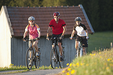Germany, Bavaria, Man and women riding bicycle - DSF000563