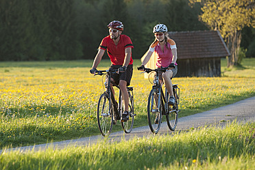 Germany, Bavaria, Man and woman riding bicycle - DSF000552