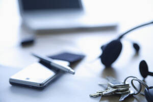Cell phone, head set and keys on office table, close up - TCF002309