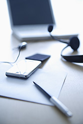 Cell phone, head set, pen and laptop on office table, close up - TCF002311