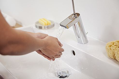 Germany, Bavaria, Young woman washing hands in bathroom sink - MAEF004592