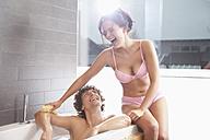 Germany, Bavaria, Young woman bathing man in bathroom - MAEF004639