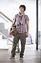Germany, Bavaria, Young man standing with bag at home - MAEF004631