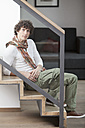 Germany, Bavaria, Young man sitting on steps at home, portrait - MAEF004634