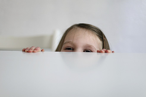 Germany, Berlin, Girl hiding at table - SAF000010