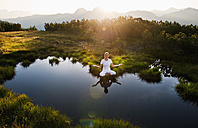 Austria, Salzburg County, Young woman sitting near mountain lake and doing meditation - HHF004071