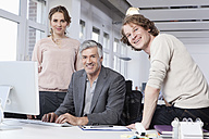 Germany, Bavaria, Munich, Men and woman using computer in office, smiling, portrait - RBYF000050
