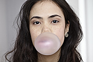 Germany, Cologne, Young woman blowing bubble gum - RHYF000082