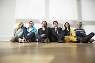 Germany, Cologne, Men and women sitting on floor - RHYF000085