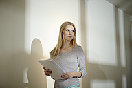 Germany, Cologne, Young woman with paper in office - RHYF000088