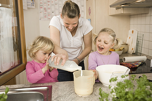 Mother and daughter pouring milk into measuring cup - RNF000916