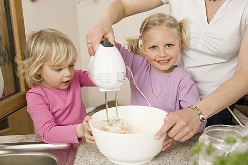 Mother and daughter mixing batter with electric whisk - RNF000919