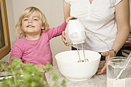 Mother and daughter mixing batter with electric whisk - RNF000922