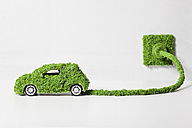 Electric car covered with grass connected to socket, close up - RBF000800