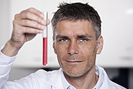 Germany, Bavaria, Munich, Scientist holding red liquid in test tube for medical research in laboratory - RBF000830