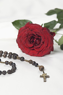 Rosary beads with red rose on bed, close up - CRF002194