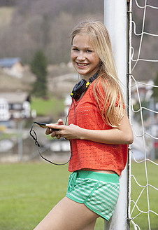 Austria, Teenage girl with handy, smiling, portrait - WWF002316