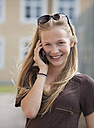 Austria, Teenage girl on mobile phone, smiling, portrait - WWF002320